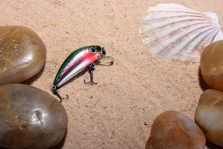 Artificial small fish - a bait for fishing in the rivers, the seas and lakes on sand with a cockleshell and pebbles.