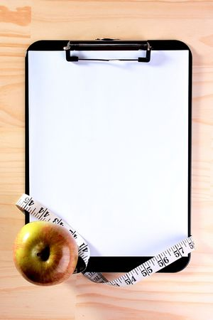 The apple, tape measure and blank clipboard for those who takes a great interest in diets.