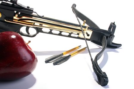 crossbow: Crossbow with arrows and a red apple. Stock Photo