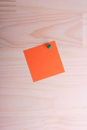 information medium: The orange standard sheet for records is pinned to the wooden panel.