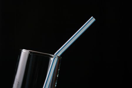 Empty glass glass with a tubule for a cocktail on a black background. Фото со стока