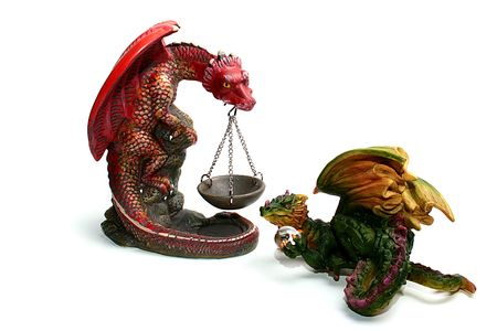 Two ceramic dragons, one holds a support for fire, the second holds a magic transparent sphere.