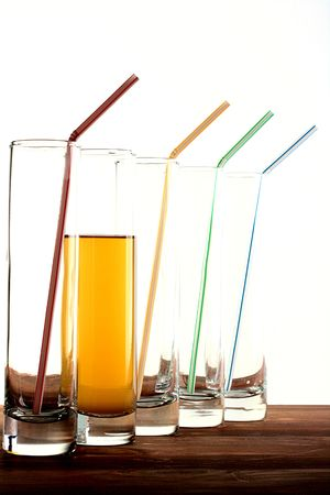 tubule: Five glasses, in four tubules for a cocktail and they empty, in the fifth are not present a tubule for a cocktail, but there is an apple juice. Stock Photo