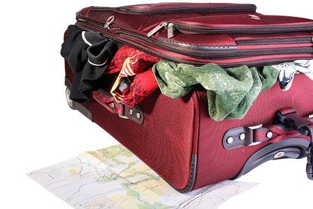 developed: Maleta grande rojo con las cosas que sobresale de ella. Una maleta en el curso de embalaje. En virtud de una maleta la tarjeta desarrollada de viaje se encuentra.