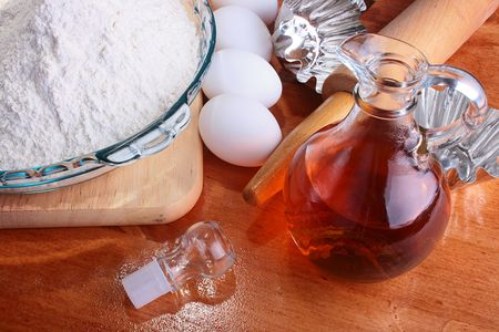The forms prepared for a batch, and also components: a flour, eggs, oil, on a chopping board with Rolling pin. Stok Fotoğraf