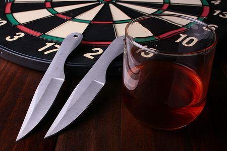 throwing knife: Two knifes for a throwing, a target and a glass of whisky. Stock Photo