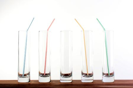 Five high narrow glasses, in four straws for a cocktail. Imagens