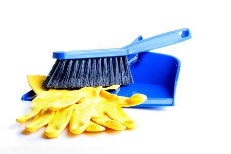 Stof pan en penseel van donker blauw kleuren met een zwarte borstel voor stof reiniging en gele rubberen hand schoenen op een witte achtergrond.  Stockfoto