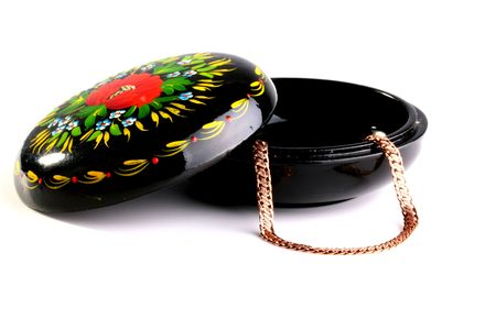 Wooden box covered with a black varnish and ornamented in Russian style. The box is intended for storage of jewelry: chains, earrings, rings. Stock Photo