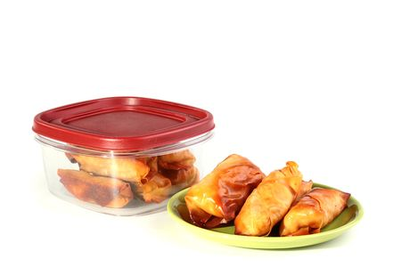 bakery products: Pancakes with meat in a plate and a plastic box for storage of products.