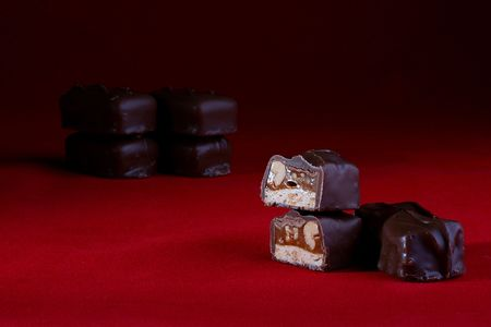 delightfully: The chocolate with nuts is cut half-and-half. A red background, on a back background some chocolates. Stock Photo