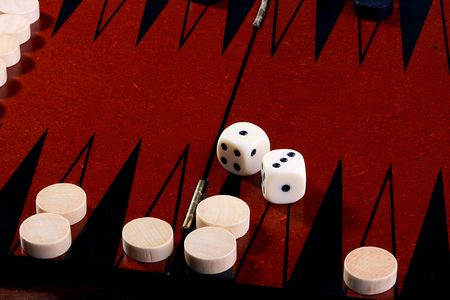 Backgammon, in the foreground in focus black counters, on a background of a counter of the contender and cubes. Imagens