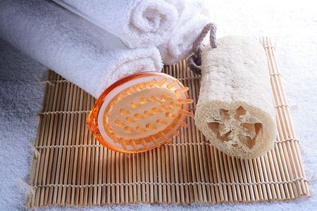 hair treatment: Terry towels with a massage brush and a bast on a laying made of a bamboo.