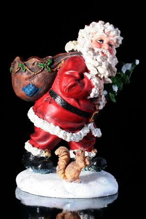 kringle: The ceramic grandfather a frost by a holiday New Year with the squirrel on a black reflecting background. Stock Photo