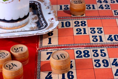 Lotto game on a table with a red cloth, a coffee cup. photo