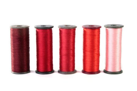 Colour threads for an embroidery on a white background. Threads on coils for industrial use. photo