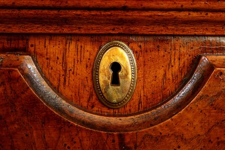 Wooden door of an ancient desk with a decorative metal plate for a key. Stock Photo - 6183335