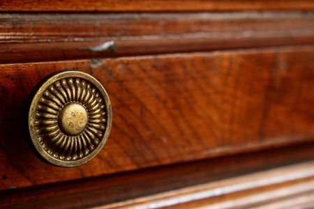 The ancient decorative handle of a box of a wooden desk. photo