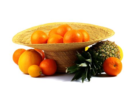 The straw farmer hat full of oranges, nearby lies pineapple, oranges, a lemon and a grapefruit. Stock Photo - 6242681
