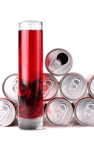 The high glass narrow glass with a drink of red colour and containers from a tin in which is stored this drink. Stock Photo - 6292286
