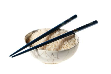 Rice in teabowl with dark blue chopsticks on a white background.