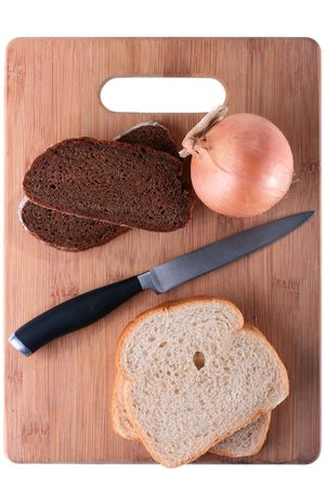 Black bread with onions is separated from a white loaf by a knife on a wooden chopping board.