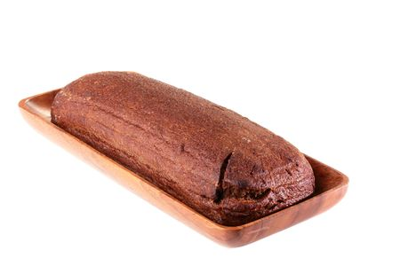 Loaf of black bread of the oblong form in a wooden plate on a white background.