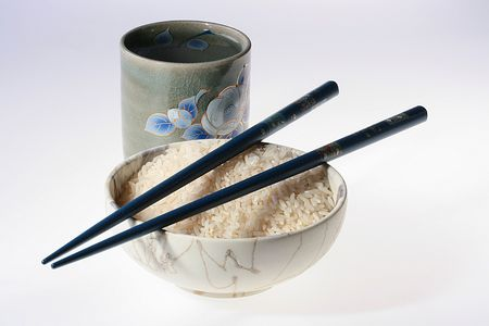 Ceramic cup with water and a deep bowl with rice, chopsticks.
