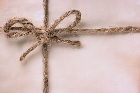 old envelope: The ancient package is tied by a cord with a bow.