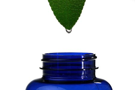 The theme of pharmaceutical homoeopathic preparations, in a picture sheet of a medicinal grass with which flows down juice in a pharmaceutical bottle of dark blue colour. Stock Photo