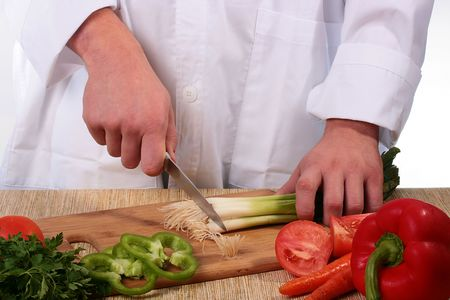 off cuts: The cook cuts off at green onions backs on a kitchen board.