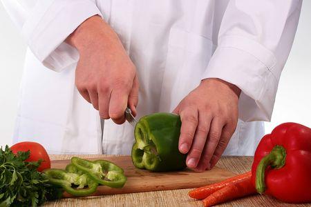 El cocinero corta sobre cocina un tablero de anillos de pimienta. Foto de archivo - 6547541