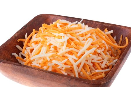 Two grades of firm cheese are grated in a wooden plate.