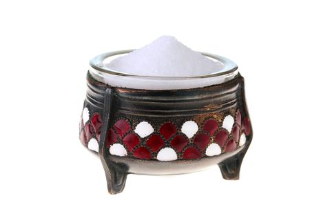 Ancient saltcellar with salt on a white background.
