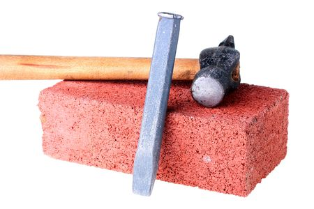Building materials and tools: a chisel and a hammer with a brick from red clay.