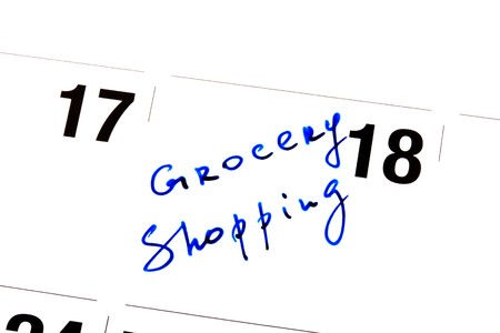 Reminder written down on a calendar about visiting of shop of Groceries.