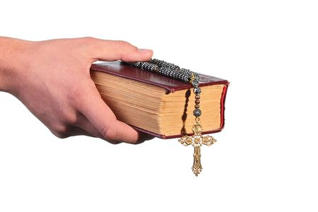 The mans hand holds the old bible with a cross on a chain.