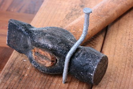 bent: The bent nail sits on a hammer, a metalwork workshop. Stock Photo
