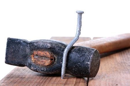 De gebogen spijker zit op een hamer, een werkplaats voor metaalbewerking.