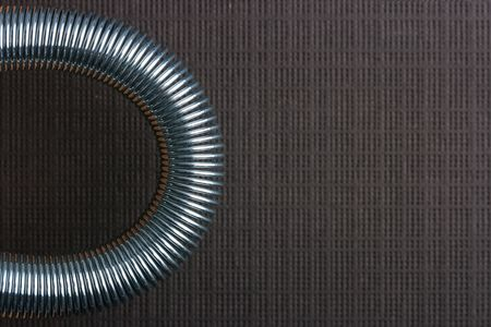 Metal spring deformed on an arch on a brown background. Stock Photo