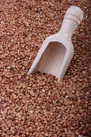 prepack: Buckwheat groats with a wooden deep spoon for packaging. Stock Photo
