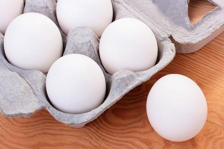흰색 색상의 계란은 운송 및 판매를위한 특수 트레이에 결합됩니다.