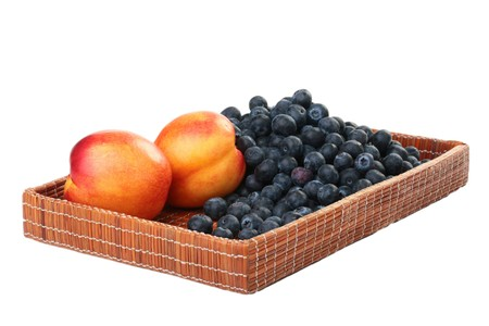 Berries of a blueberry and nectarine in a deep wattled tray.