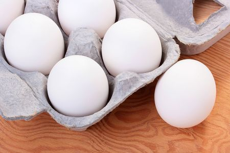 Eggs of white colour are combined in a special tray for transportation and sale.