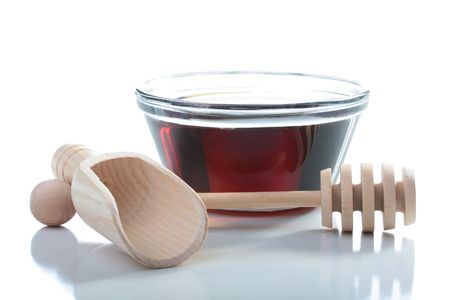 Honey in glasswares with wooden honey dipper.