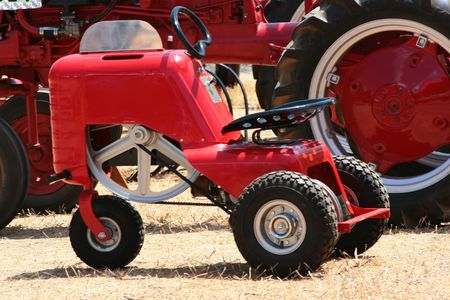Small tractor of red colour against the big tractor. Imagens