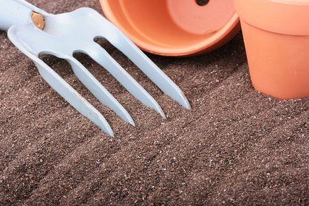 Steel rake on a ground near to ceramic pots. Stok Fotoğraf
