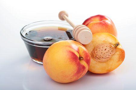 白い背景に滑らかな桃と蜂蜜。