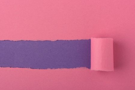 Background consisting of two sheets of paper pink and violet. The top layer is broken off.