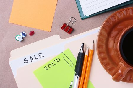 A manila sale folder laying next to a cup of coffee and office materials. Stock Photo - 7422988